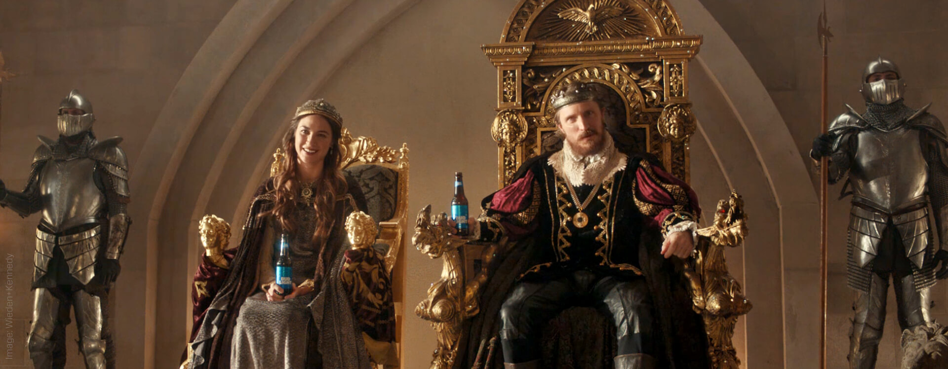 Bud light advertisement image, King and Queen drinking bud light while sitting on a throne