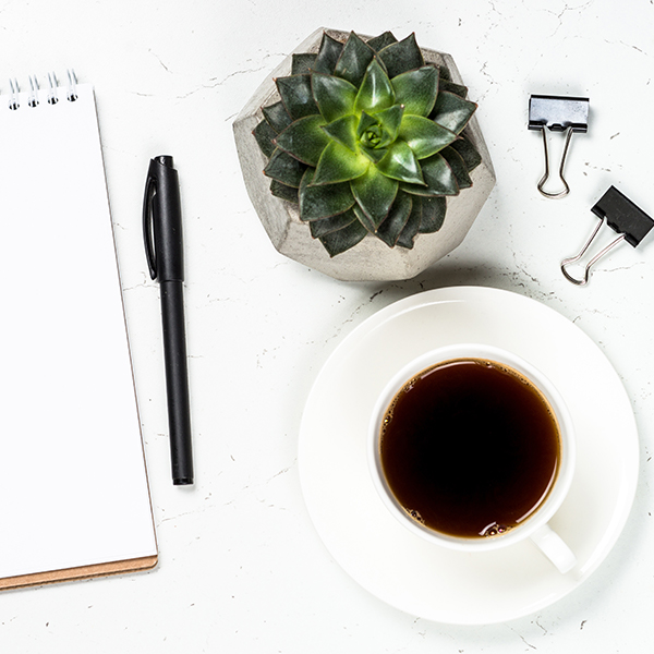 White coffee cup next to a plant and black pen on a white table